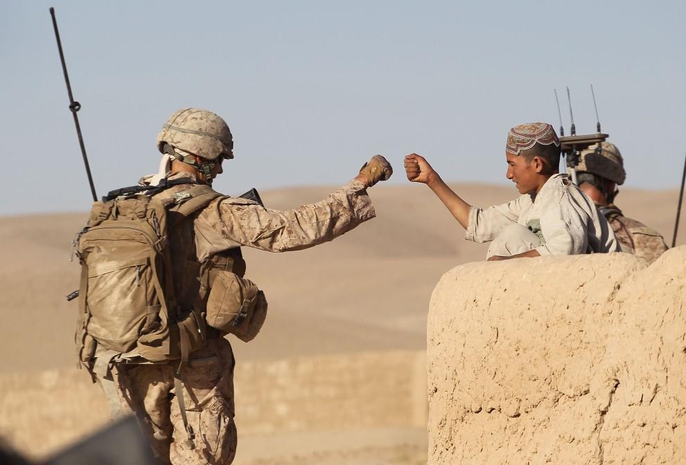 """27. AFGANISTAN, Kajaki, 9 października 2010: Amerykański żołnierz na patrol """"przybija żółwika"""" z afgańskim chłopcem. (Foto: Scott Olson/Getty Images)"""