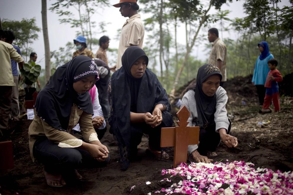 32. INDONEZJA, Yogyakarta, 28 października 2010: Kobiety modlą się nad mogiłą ofiary erupcji wulkanu. (Foto: Ulet Ifansasti/Getty Images)