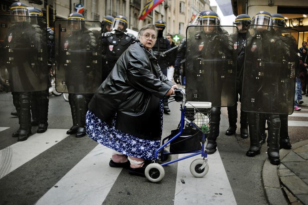 35. FRANCJA, Dijon, 15 października 2010: Kobieta przygląda się zamieszkom na ulicy w Dijon. AFP PHOTO / JEFF PACHOUD