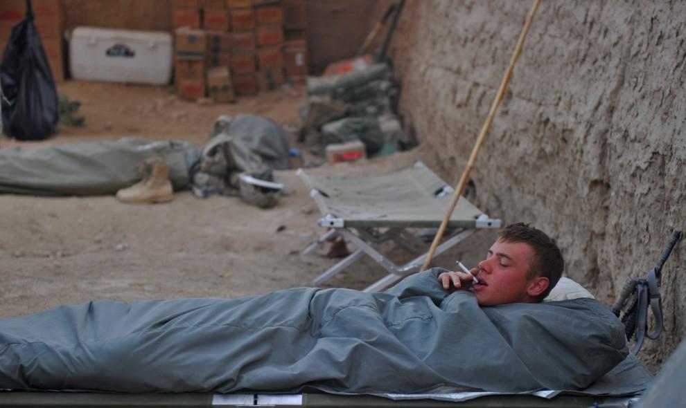 35. AFGANISTAN, Kandahar, 24 października 2010: Amerykański żołnierz pali w łóżku w obozie Siah Choy. AFP PHOTO/Massoud HOSSAINI
