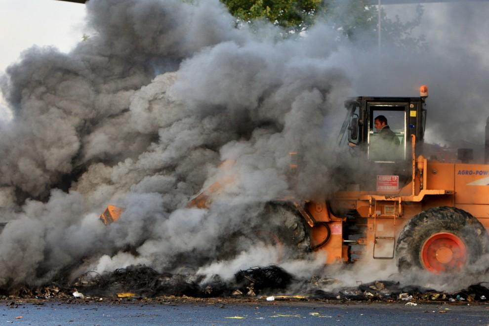39. FRANCJA, Caen, 19 października 2010: Buldożer usuwa z ulicy płonącą barykadę. AFP PHOTO KENZO TRIBOUILLARD