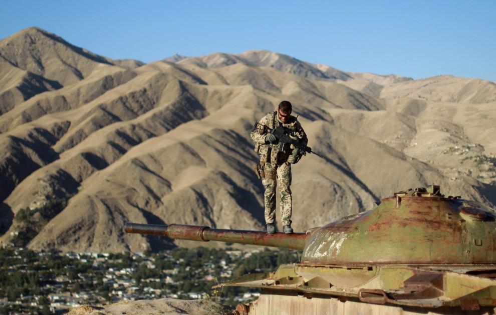 3.  AFGANISTAN, Fajzabad 1 października 2010: Żołnierz balansuje na lufie zniszczonego czołgu. (Foto: Miguel Villagran/Getty Images)