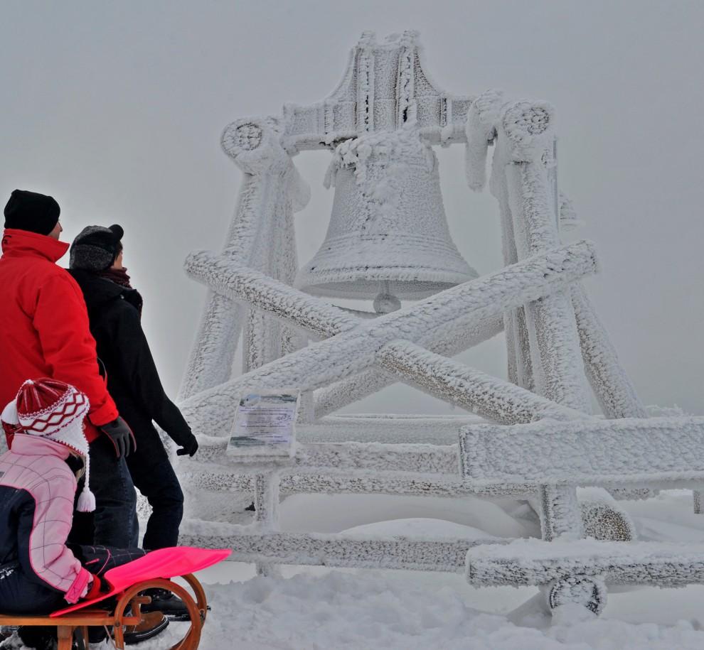 10. NIEMCY, Oberwiesenthal, 27 listopada 2010: Turyści przyglądają się pokrytemu szronem i śniegiem dzwonowi. AFP PHOTO / HENDRIK SCHMIDT