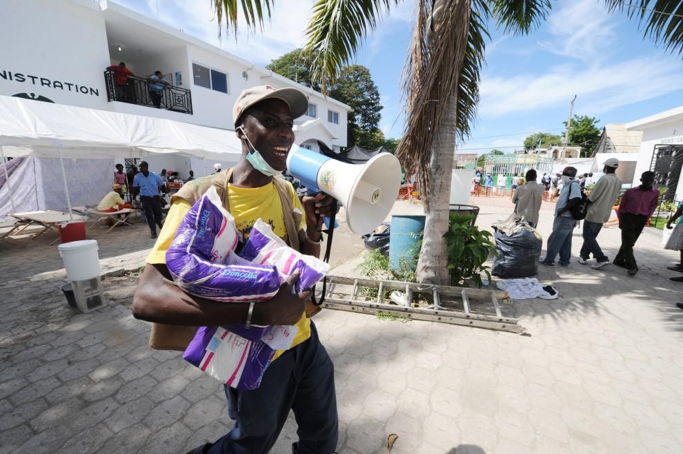 10. HAITI, St. Marc, 24 października 2010: Pracownik szpitala Św. Mikołaja przekazuje informacje zgromadzonym ludziom. AFP PHOTO / Thony BELIZAIRE