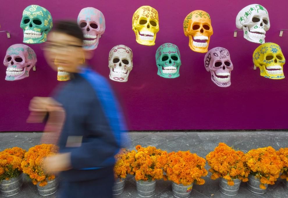 """13. MEKSYK, Meksyk, 1 listopada 2010: Maski-czaszki oraz kwiaty (aksamitki wzniesione, nazywane tutaj """"kwiatami zmarłych"""") sprzedawane przed wejściem na cmentarz w stolicy Meksyku. AFP PHOTO/Alfredo Estrella"""
