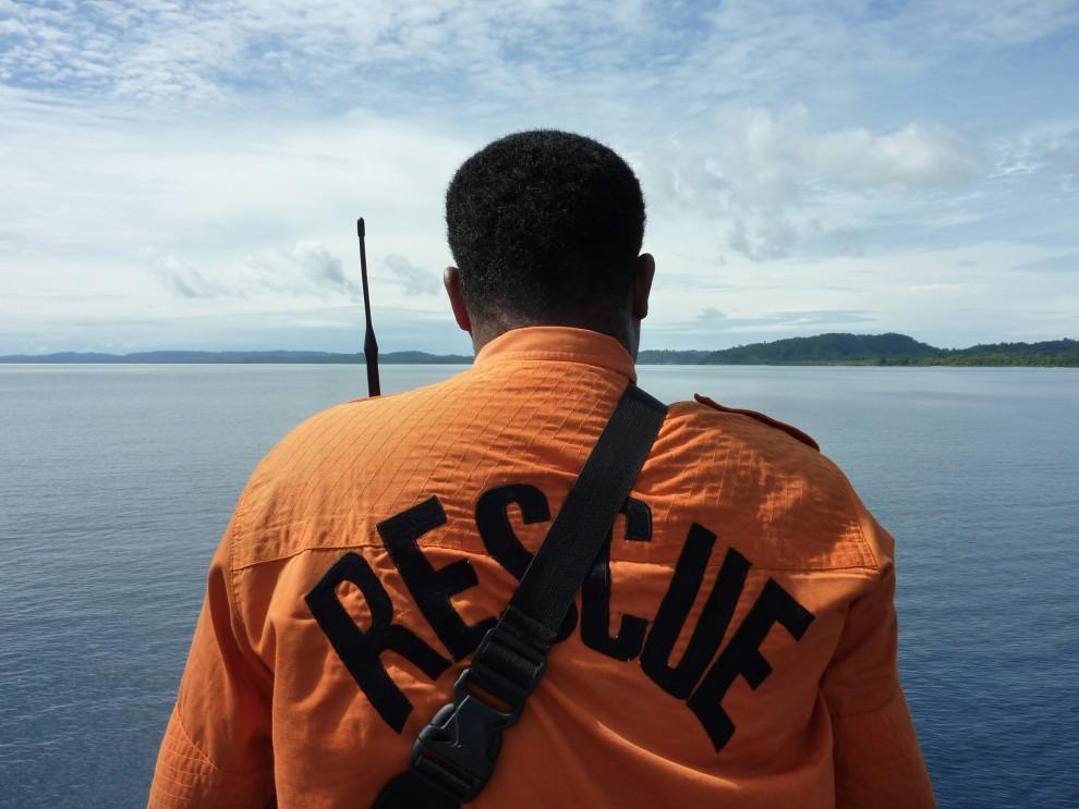 13. INDONEZJA, Pagai, 29 listopada 2010: Członek ekipy ratunkowej na pokładzie łodzi z pomocą dla ofiar erupcji. AFP PHOTO / BAY ISMOYO