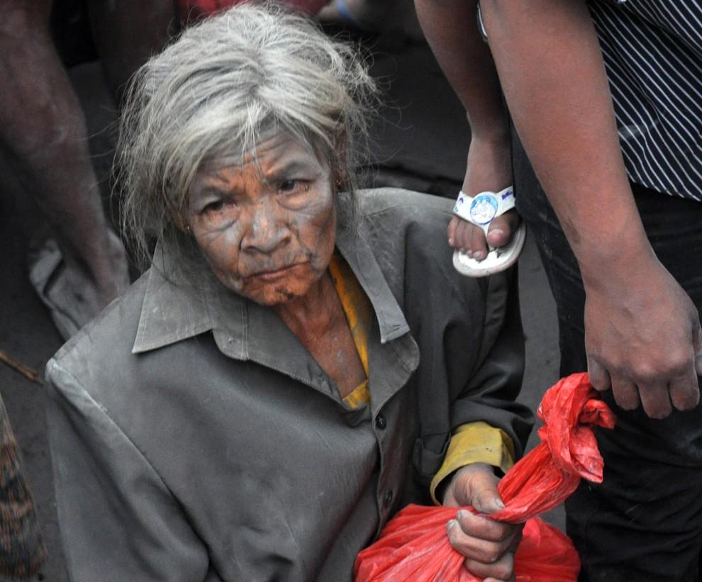 14. INDONEZJA, Argomulyo, 5 listopada 2010: Ewakuowana kobieta ściska w dłoni plastikową torbę z rzeczami osobistymi. AFP PHOTO / ALTAMIRA