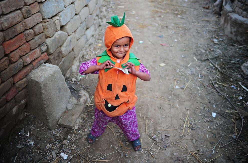 18. PAKISTAN, Islamabad, 29 października 2010: Dziewczynka ze slumsów na przedmieściach Islamabadu w kostiumie na Halloween. AFP PHOTO/Carl de Souza
