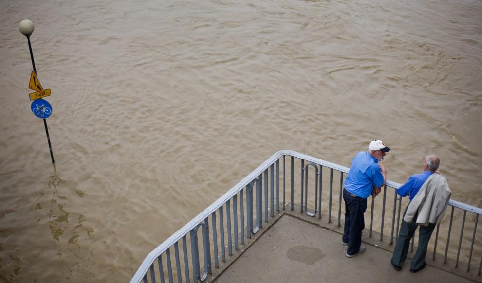 17. POLSKA, Warszawa, 9 czerwca 2010: Mężczyźni obserwują drugą falę kulminacyjną przepływającą przez stolicę. AFP PHOTO WOJTEK RADWANSKI