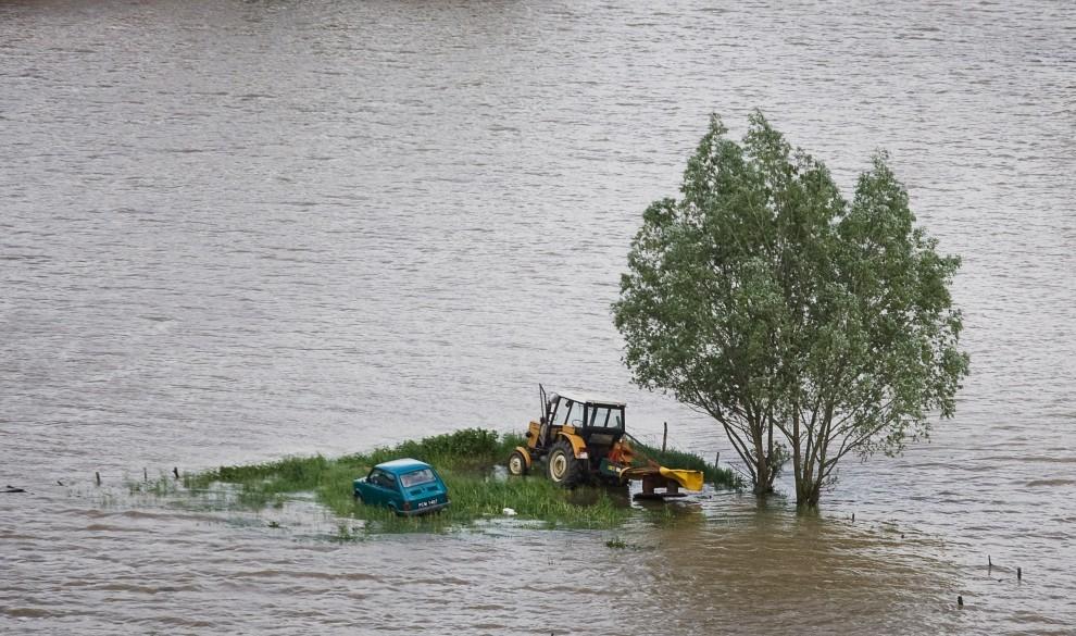 """18. POLSKA, Świniary, 25 maja 2010: Ciągnik i """"maluch"""" zaparkowane na wzniesieniu w zatopionej przez powódź we wsi Świniary. AFP PHOTO WOJTEK RADWANSKI"""
