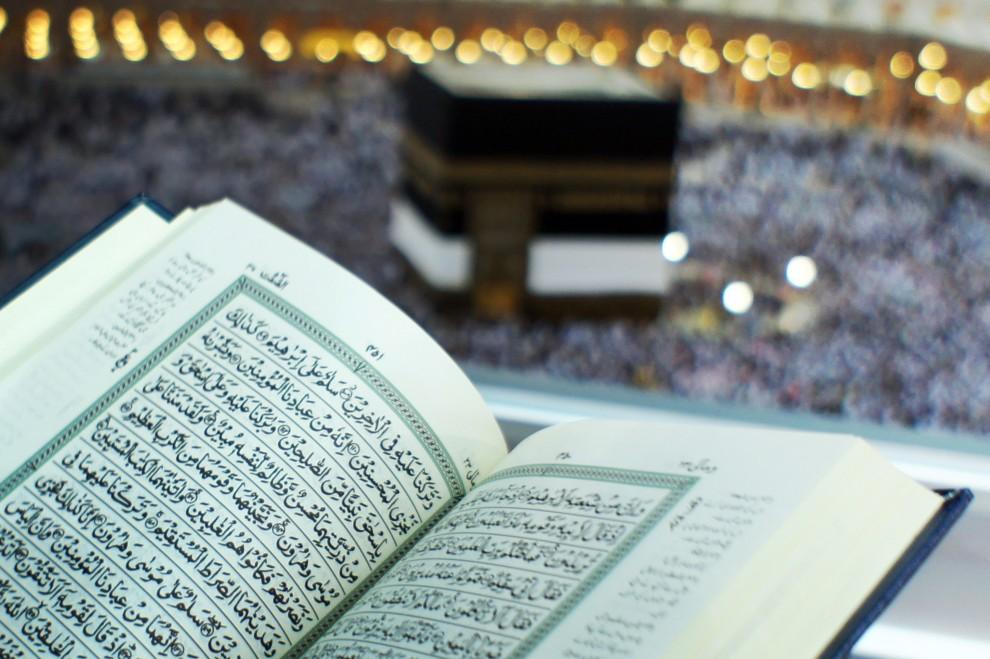 1. ARABIA SAUDYJSKA, Mekka, 9 listopada 2010: Otwarta święta księga muzułmanów – Koran – na tle Kaaby, w meczecie Al-Masjid al-Ḥarām. AFP PHOTO / MUSTAFA OZER