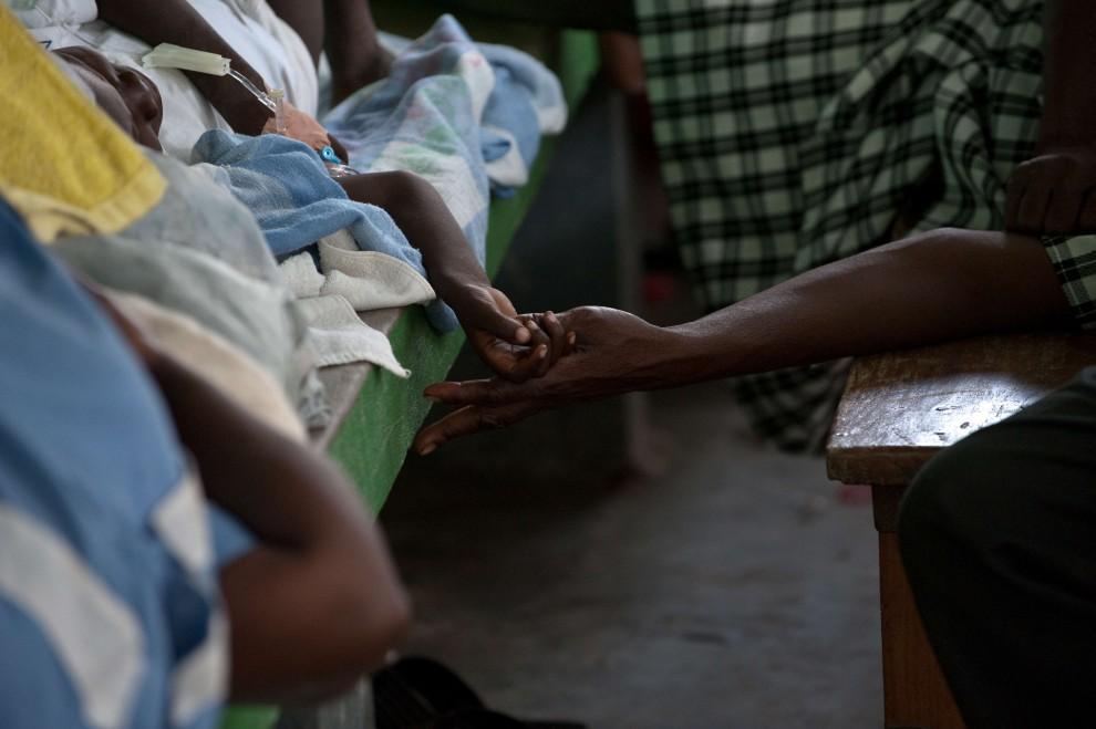 20. HAITI, Petite Riviere, 28 października 2010: Mężczyzna trzyma za rękę synka cierpiącego w wyniku odwodnienia. AFP PHOTO/Nicholas KAMM