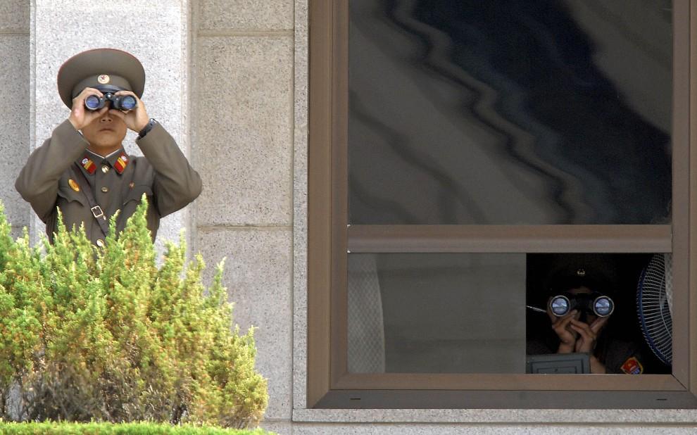 21. KOREA POŁUDNIOWA, Panmundżom, 22 czerwca 2007: Północnokoreańscy żołnierze obserwuje pas ziemi w strefie zdemilitaryzowanej. AFP PHOTO/KIM JAE-HWAN