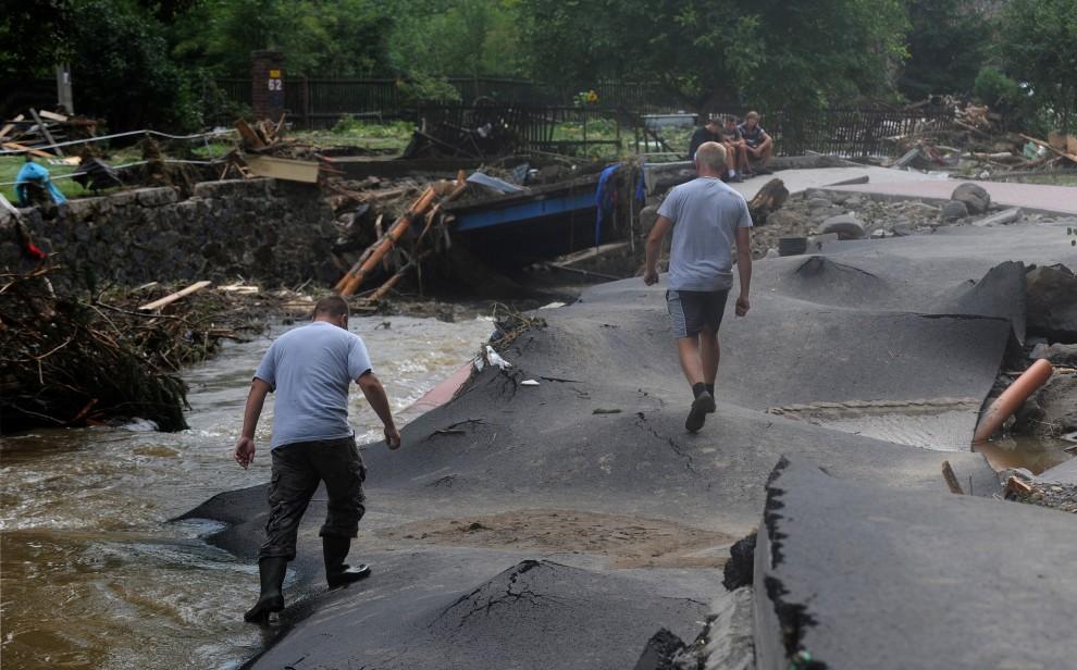 21. POLSKA, Bogatynia, 8 sierpnia 2010: Mężczyźni idą drogą zniszczoną podczas powodzi. AFP PHOTO/ MICHAL CIZEK