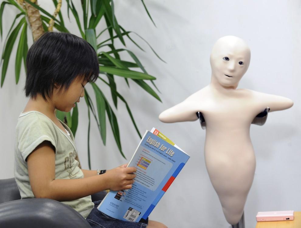 """25. JAPONIA, Osaka, 1 sierpnia 2010: Dziewczynka podczas lekcji prowadzonej przez robota o nazwie """"Telenoid R1"""". AFP PHOTO / Yoshikazu TSUNO"""