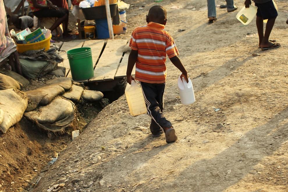 27. HAITI, Port-au-Prince, 26 października 2010: Chłopiec niesie do swojego tymczasowego domu pojemniki z wodą. (Foto: Spencer Platt/Getty Images)