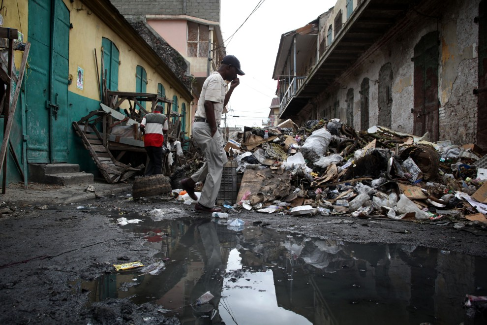 28. HAITI, Cap-Haitien, 19 listopada 2010: Mężczyzna przechodzi obok sterty śmieci przy zamkniętym bazarze w Cap-Haiten. AFP PHOTO/JULIEN TACK