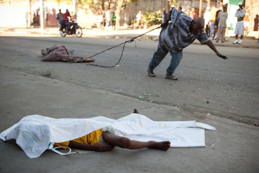 2. HAITI, Cap-Haitien, 19 listopada 2010: Obok leżących na ulicy zwłok, Mężczyzna ciągnie ciało kolejnej ofiary cholery. AFP PHOTO/JULIEN TACK