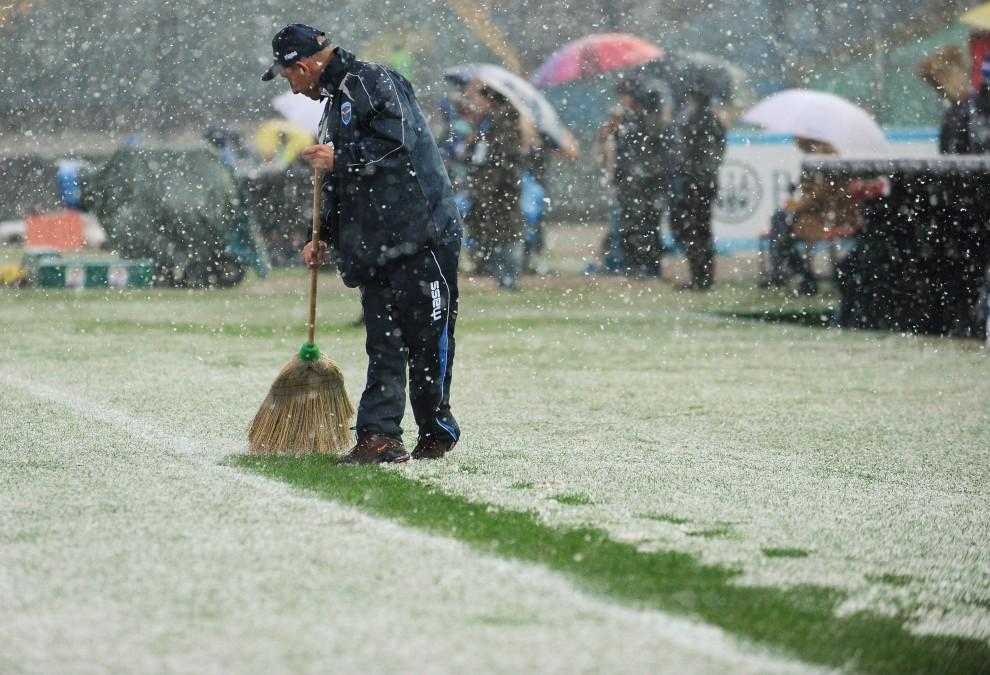 2. WŁOCHY, Brescia, 28 listopada 2010: Pracownik techniczny odsnieża linie boiska przed meczem Serie A. (Foto: Valerio Pennicino/Getty Images)