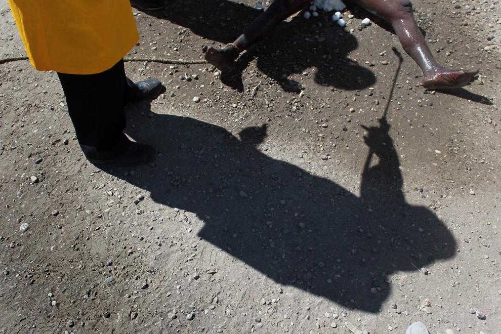 32. HAITI, Port-au-Prince, 17 listopada 2010: Pracownik ekipy sanitarnej spryskuje ciało ofiary cholery. (Foto: Joe Raedle/Getty Images)
