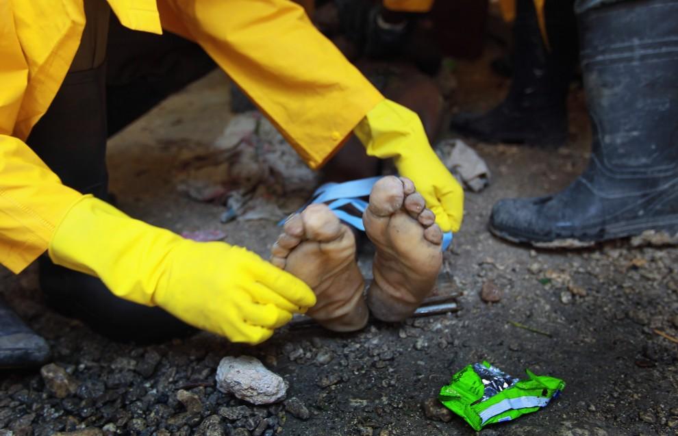 35. HAITI, Port-au-Prince, 20 listopada 2010: Pracownicy jednej z ekip sanitarnych przygotowują ciało Nixona Merise (24 lata) do wywiezienia z rodzinnego domu, w którym zmarł na cholerę. (Foto: Joe Raedle/Getty Images)