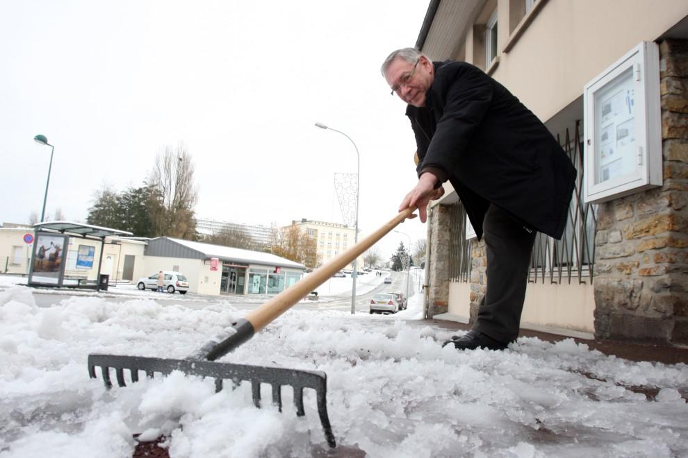 3. FRANCJA, Cherbourg-Octeville, 27 listopada 2010: Mężczyzna usuwa grabiami śnieg z chodnika. AFP PHOTO KENZO TRIBOUILLARD