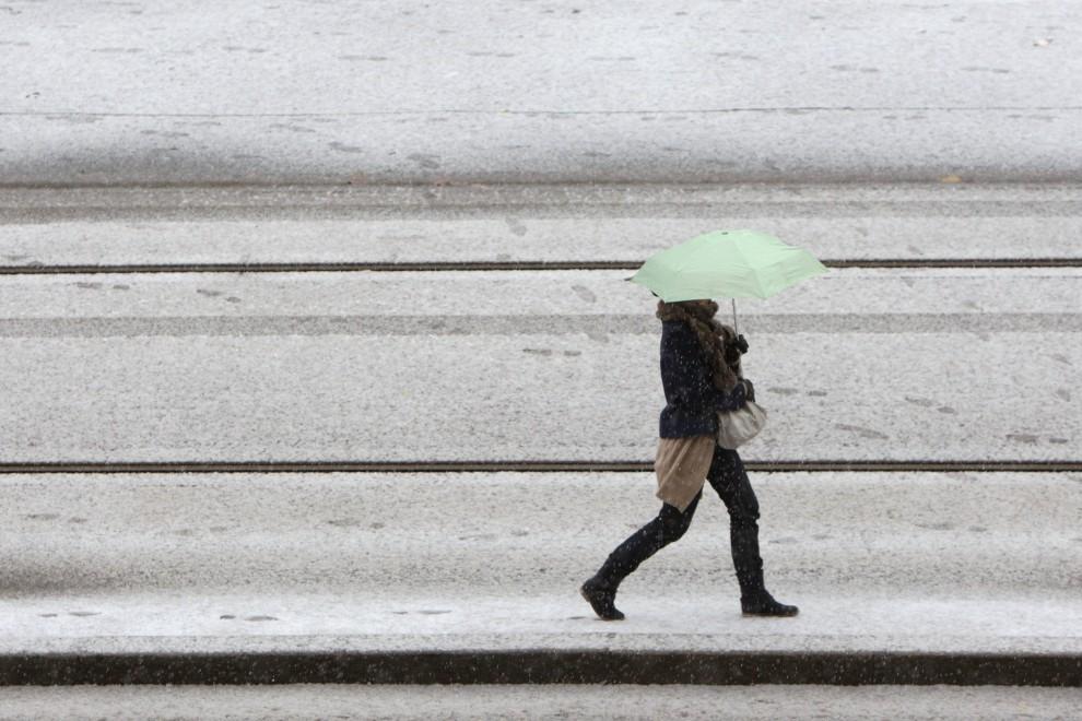 4. FRANCJA, Caen, 25 listopada 2010: Kobieta chowa się pod parasolem przed obfitymi opadami śniegu. AFP PHOTO/KENZO TRIBOUILLARD