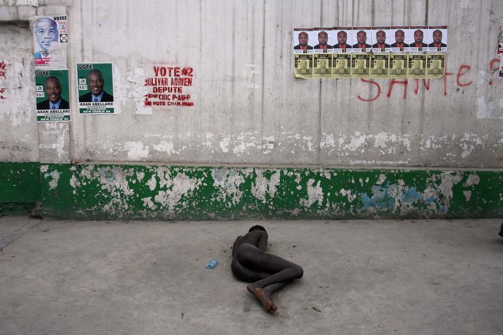 4. HAITI, Port-au-Prince, 16 listopada 2010: Naga kobieta leży na ulicy w pobliżu szpitala gdzie leczeni są chorzy na cholerę. AFP PHOTO / Hector RETAMAL