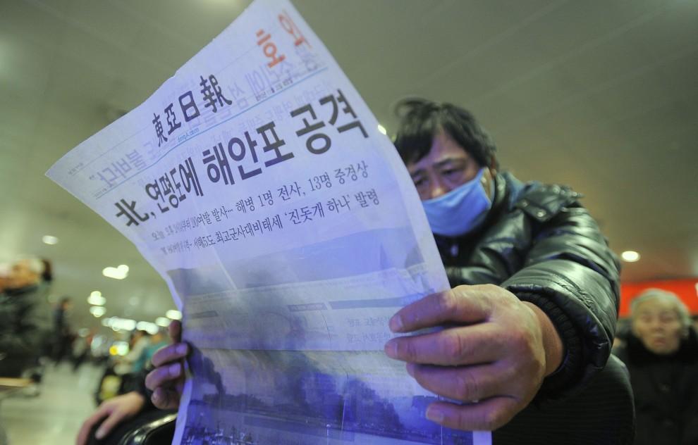 4. KOREA POŁUDNIOWA, Seul, 23 listopada 2010: Mężczyzna czekający na autobus czyta specjalne wydanie jednej z gazet. AFP PHOTO / PARK JI-HWAN