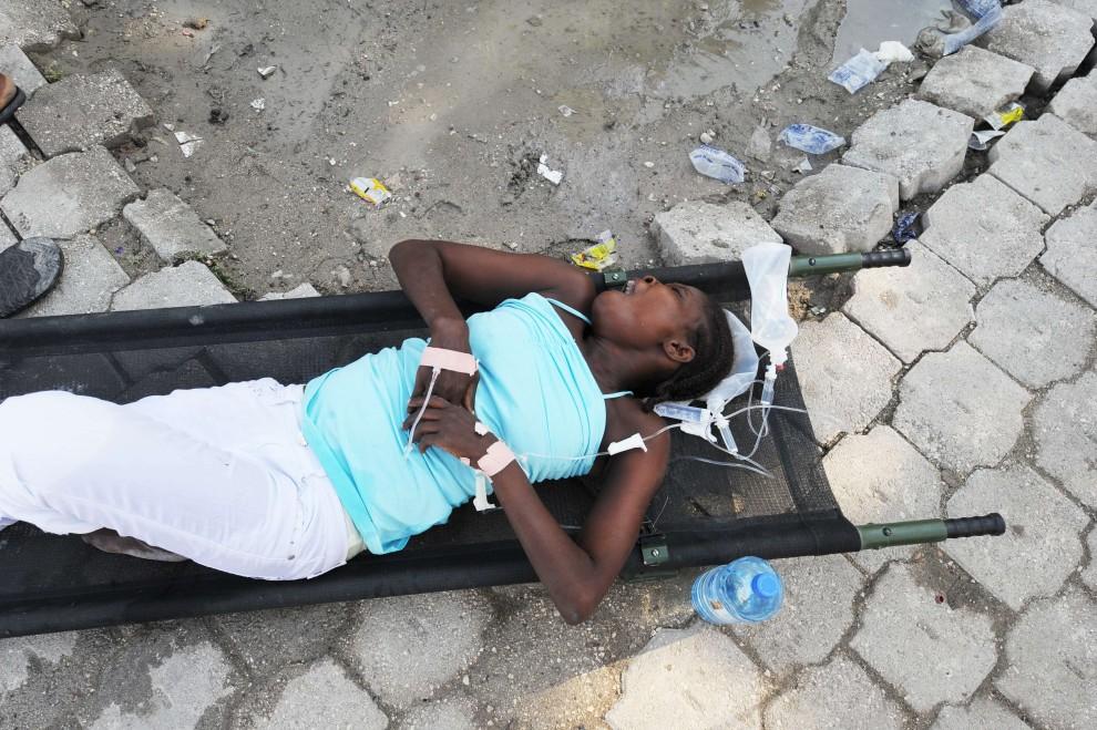 5. HAITI, Port-au-Prince, 22 października 2010: Chora czeka na lekarza w pobliżu szpitala. AFP PHOTO Thony BELIZAIRE