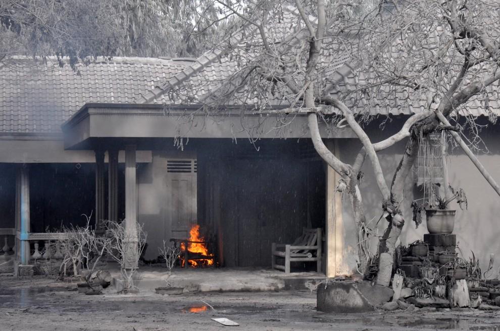 5. INDONEZJA, Argomulyo, 5 listopada 2010: Płonący fotel przy wejściu do zasypanego pyłem wulkanicznym domu. AFP PHOTO / ALTAMIRA