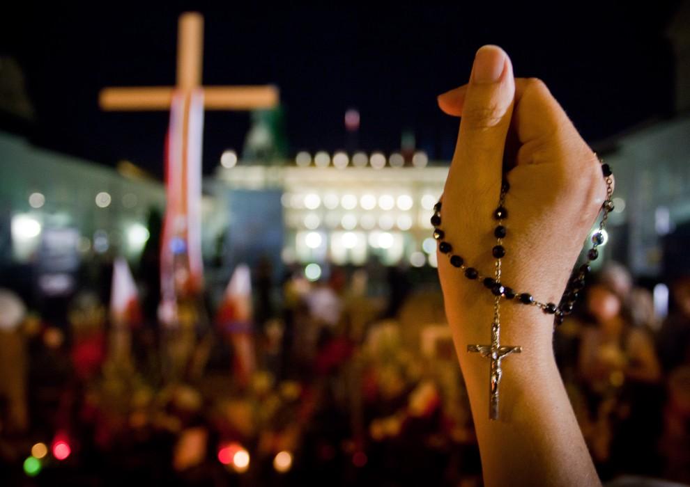 6. POLSKA, Warszawa, 10 sierpnia 2010: Różaniec opleciony wokół dłoni kobiet modlącej się pod krzyżem przed Pałacem Prezydenckim. AFP PHOTO WOJTEK RADWANSKI