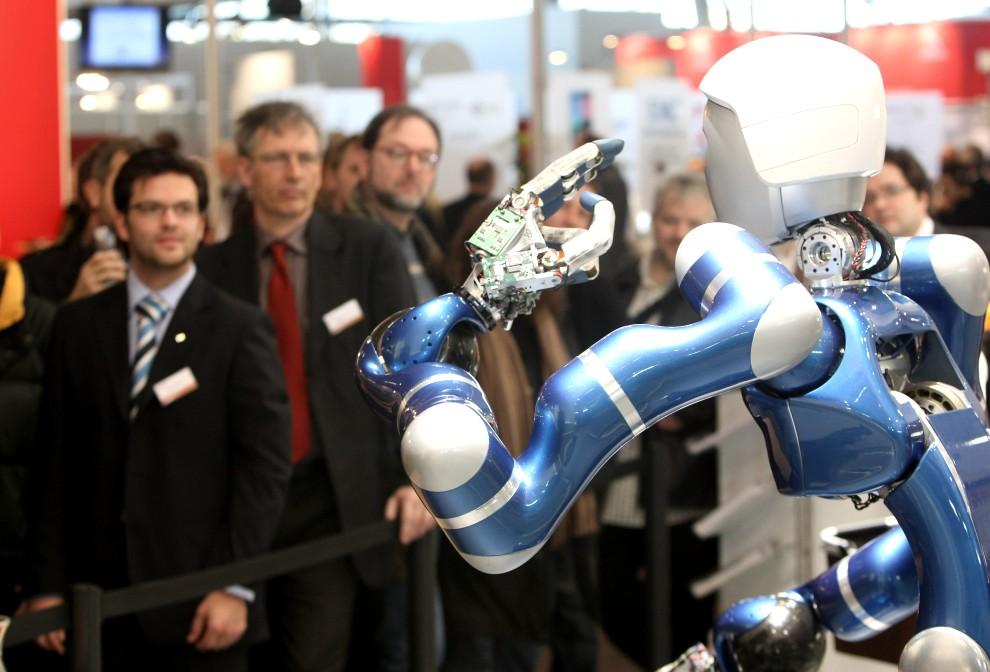 """6. NIEMCY, Hanower, 4 marca 2009: Goście targów CeBIT oglądają robota o nazwie """"Rollin Justin"""". (Foto: Sean Gallup/Getty Images)"""