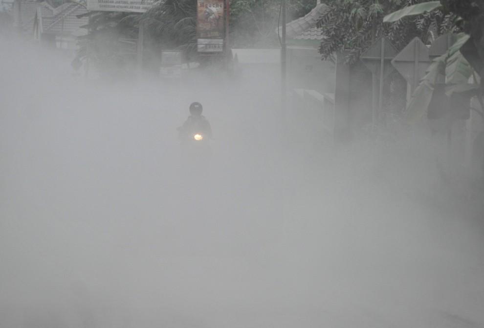 7. INDONEZJA, Yogyakarta, 6 listopada 2010: Motocyklista na zasłoniętej przez pył wulkaniczny ulicy. AFP PHOTO / Bay ISMOYO
