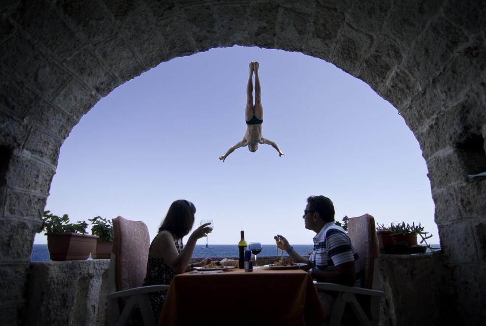10. WŁOCHY, Polignano a Mare, 5 sierpnia 2010: Australijczyk Steve Black skacze do wody podczas zawodów Red Bull Cliff Diving World Series. AFP PHOTO/Dean TREML/HO