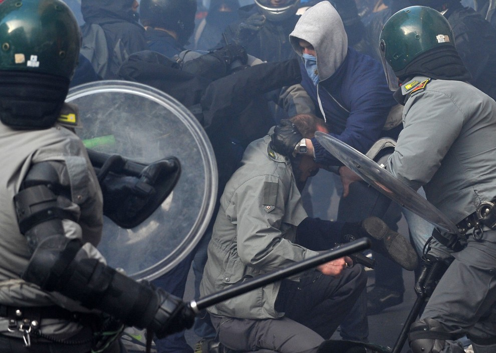 10. WŁOCHY, Rzym, 14 grudnia 2010: Policjant (trzyma pistolet) w cywilnym ubraniu atakowany przez protestujących. AFP PHOTO / ALBERTO PIZZOLI ALTERNATIVE CROP