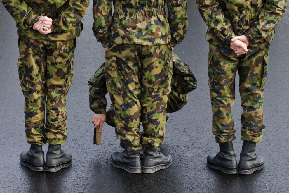 10. SZWAJCARIA, Kloten, 25 listopada 2010: Żołnierz czyści butów kolegów przed oficjalnym powitaniem prezydenta Turcji. AFP PHOTO / FABRICE COFFRINI