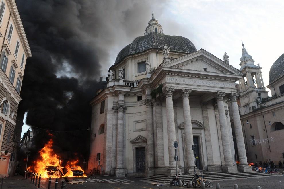 11. WŁOCHY, Rzym, 14 grudnia 2010: Radiowóz i drugi samochód podpalone przez protestujących na Piazza del Popolo. AFP PHOTO / ALBERTO PIZZOLI ALTERNATIVE CROP