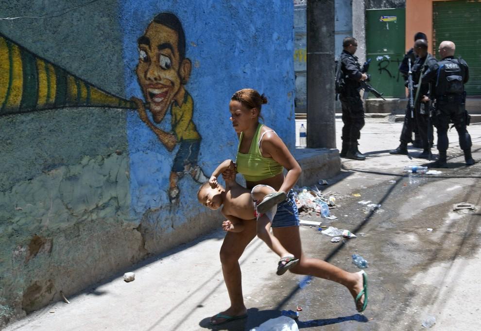 11. BRAZYLIA, Rio de Janeiro, 28 listopada 2010: Kobieta ucieka z dzieckiem ze strefy objętej działaniami policyjnymi. AFP PHOTO/Jefferson BERNARDES