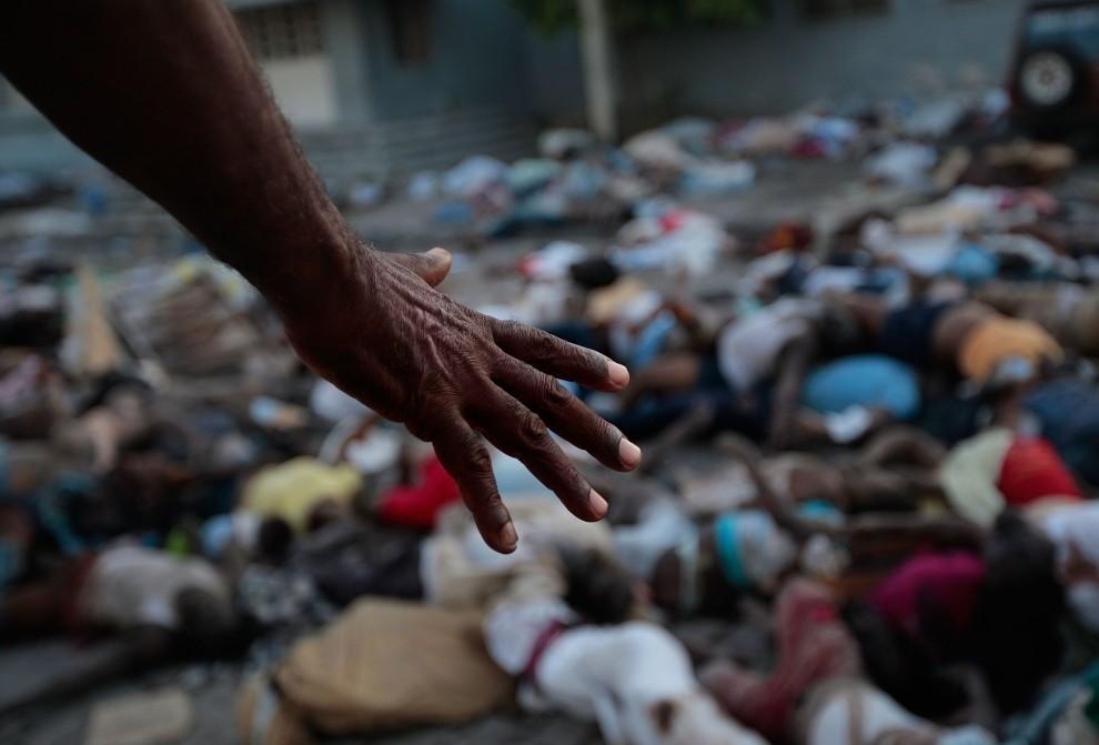 11. HAITI, Port-au-Prince, 15 stycznia 2010: Dłoń mężczyzny wskazuje na setki ciał ofiar trzęsienia ziemi. (Foto: Chris Hondros/Getty Images)