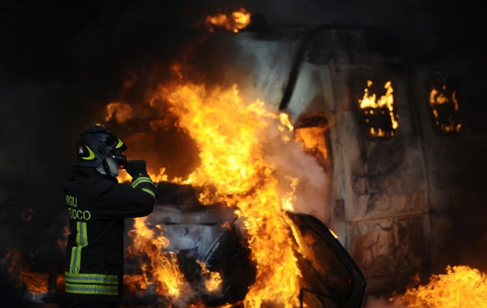 12. WŁOCHY, Rzym, 14 grudnia 2010: Strażak stara się ugasić płonące na ulicy samochody. AFP PHOTO / FILIPPO MONTEFORTE