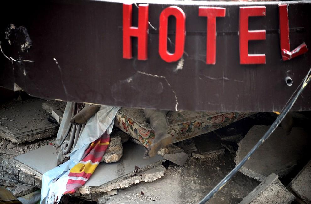 12. HAITI, Port-au-Prince, 13 stycznia 2010: Ciało ofairy trzęsienia ziemi pod gruzami zniszczonego hotelu. AFP PHOTO/Juan BARRETO