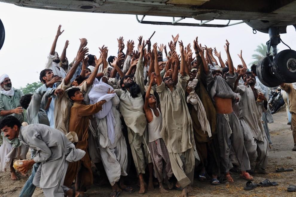 12. PAKISTAN, Lal Pir, 7 sierpnia 2010: Ludzie wyciągają ręce po żywność podawaną z pokładu śmigłowca. AFP PHOTO/Arif ALI