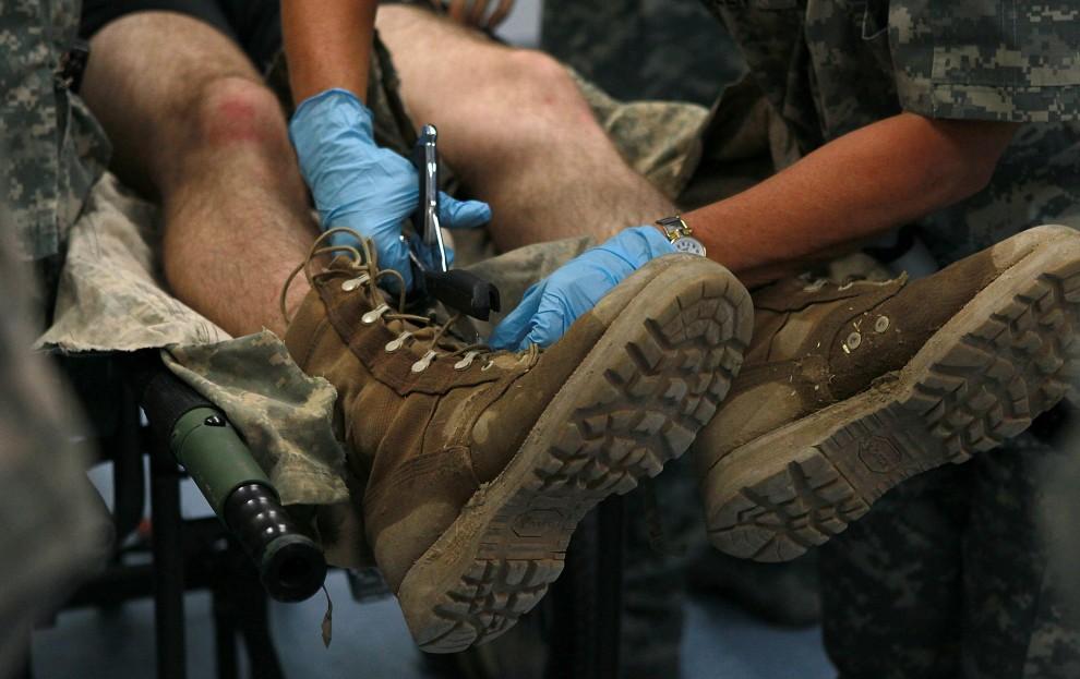 12. AFGANISTAN, Kandahar, 11 lipca 2010: Sanitariusze przygotowują rannego żołnierza do zabiegów hospitalizacyjnych. (Foto: Justin Sullivan/Getty Images)