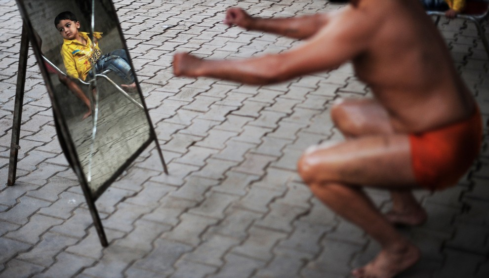 13. PAKISTAN, Lahore, 11 października 2010: Mały chłopiec przygląda się trenującym zapaśnikom. AFP PHOTO/Carl de Souza