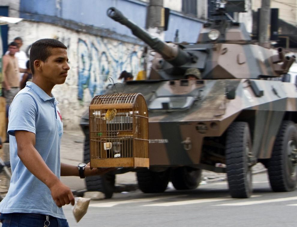 13. BRAZYLIA, Rio de Janeiro, 27 listopada 2010: Mieszkaniec faweli Morro de Alemao mija posterunek wojskowy. AFP PHOTO/Jefferson BERNARDES