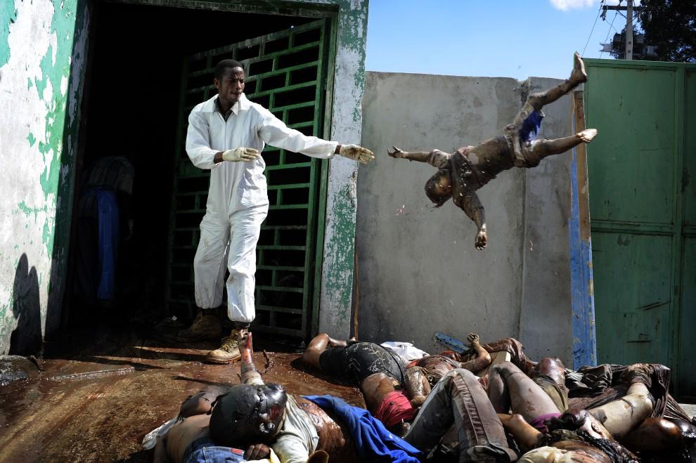 13. HAITI, Port-au-Prince, 15 stycznia 2010: Mężczyzna rzuca zwłokami w kostnicy miejskiej w Port-au-Prince. AFP PHOTO OLIVIER LABAN-MATTEI