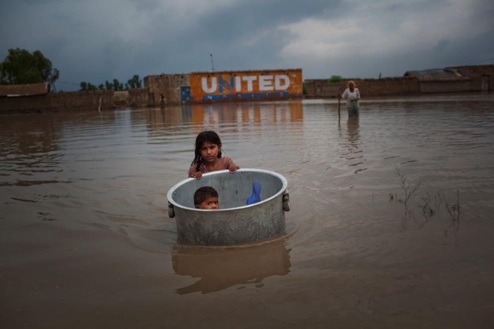 13. PAKISTAN, Sukkur, 7 sierpnia 2010: Dziewczynka ratuje swojego młodszego brata z podtopionego przez powódź domu. (Foto: Daniel Berehulak/Getty Images)