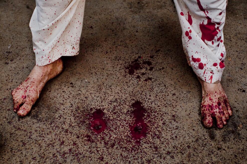 13. INDIE, New Delhi, 17 grudnia 2010: Zakrwawione stopy biczownika i ulica w trakcie obchodów Aszury. (Foto: Daniel Berehulak/Getty Images)