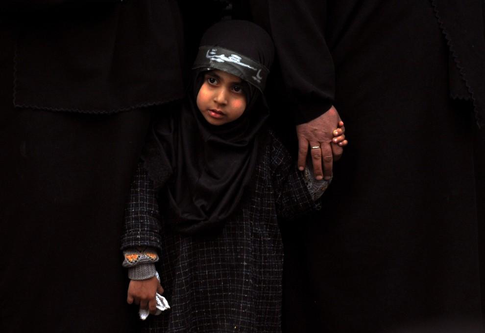 14. INDIE, Śrinagar, 17 grudnia 2010: Dziewczynka ogląda procesję biczowników. AFP PHOTO / Tauseef MUSTAFA